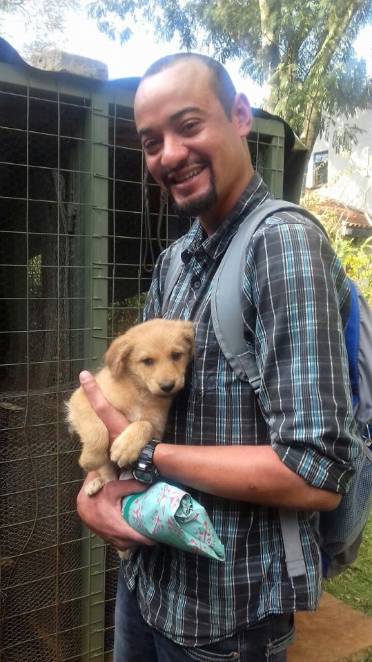 A happy new adopter picking up puppy Rakker