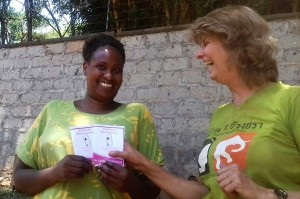 TNR Trustee Carla handing over Blackie's vaccination certificate to Lucy